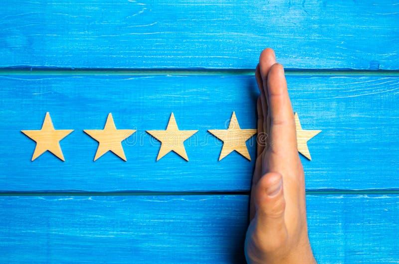 La main divise la cinquième étoile des quatre autres Évaluation de 5 étoiles, 4 étoiles Aperçu de restaurant, hôtel, café Le dete images stock