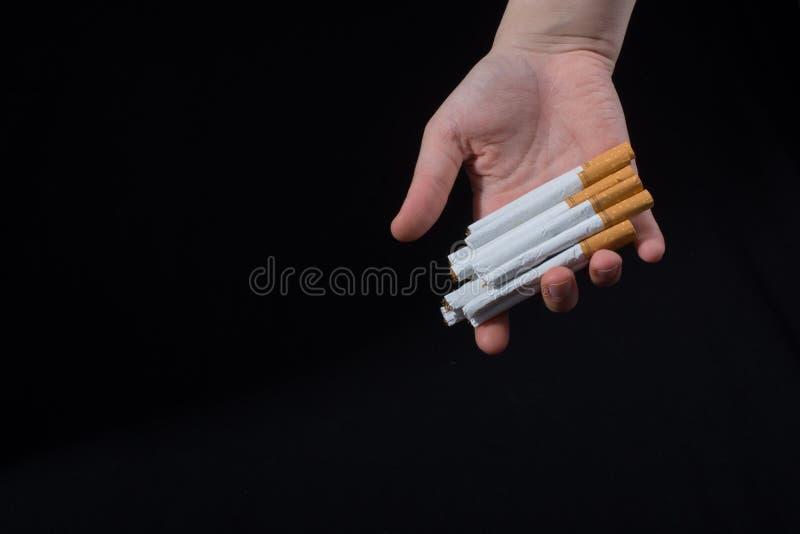 La main donne le paquet de cigarettes sur le noir images libres de droits