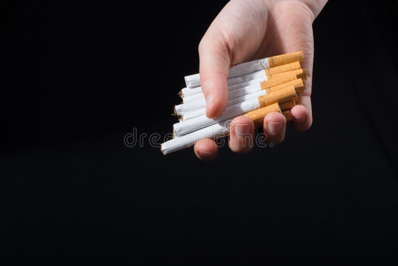 La main donne le paquet de cigarettes sur le noir image stock