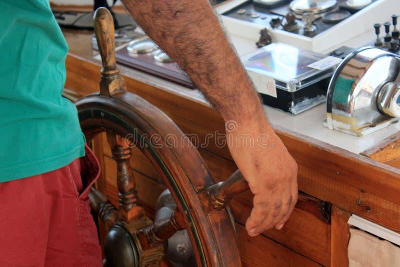 La main du capitaine tenant le volant du navire de navigation photographie stock