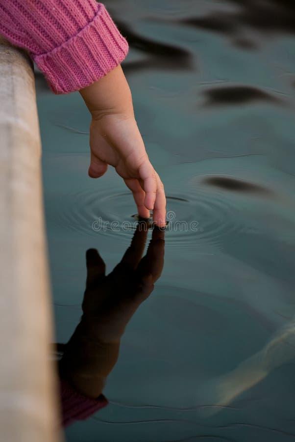 La main du gosse atteignant dans l'étang photos stock