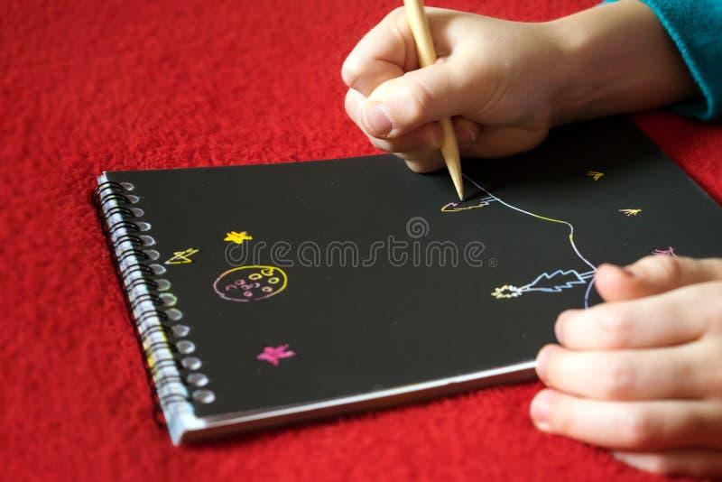 La main du ` s d'enfant dessine un dessin de paysage dans un carnet avec le noir image stock