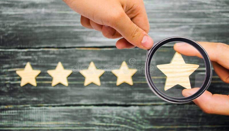 La main du ` s d'homme d'affaires tient la cinquième étoile Une nouvelle étoile, réalisent images stock