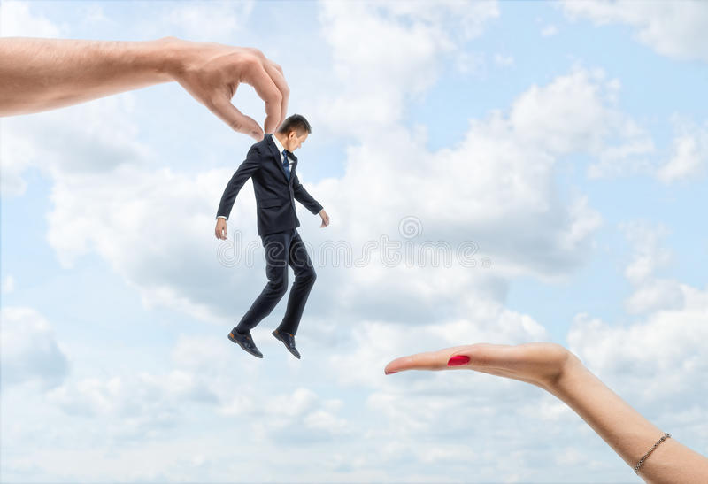 La main du ` s d'homme porte un petit homme d'affaires à une main du ` s de femme sur le backgroung du ciel bleu images stock