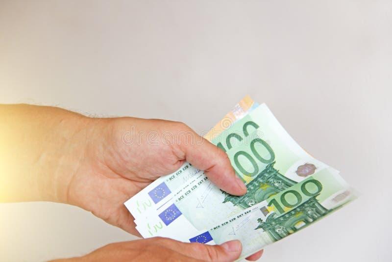 La main du ` s d'homme tient l'euro 100, les considère et paye Euros de monnaie fiduciaire dans les mains photographie stock