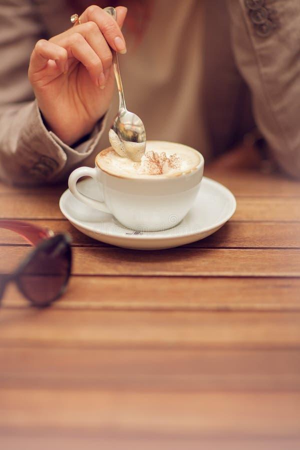 La main du ` s de jeune femme tenant une cuillère, remuent une tasse de café dans un café de rue sur une table en bois images libres de droits