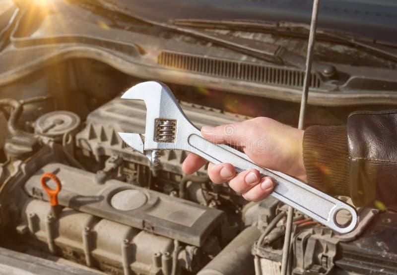 La main du ` s de mécanicien tient la clé réglable pour la réparation, sur le fond du moteur du ` s de voiture photographie stock libre de droits