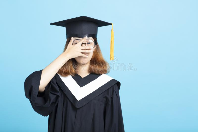 La main effrayée de fille d'obtention du diplôme couvrent les yeux photos stock