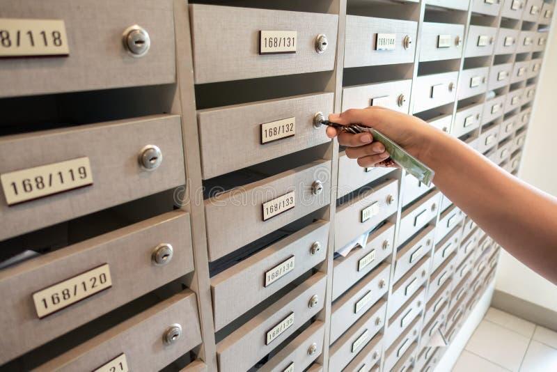 La main en gros plan de femme insèrent une clé pour ouvrir le casier de boîte aux lettres en appartement, Cabinet intérieur de bo photos stock