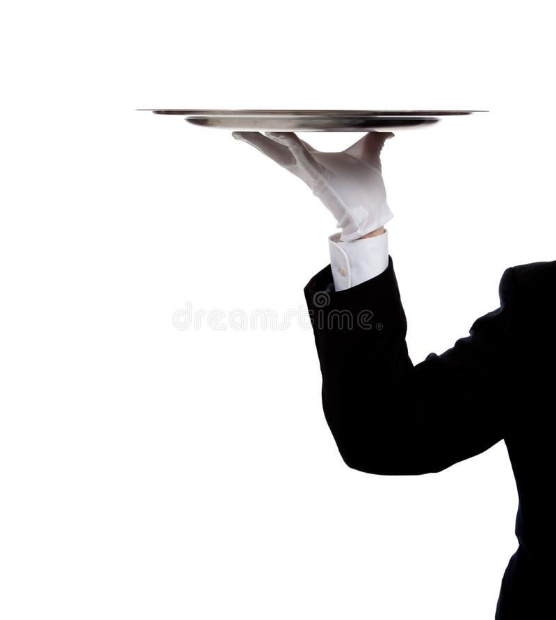 La main enfilée de gants d'un maître d'hôtel retenant un plateau argenté image libre de droits