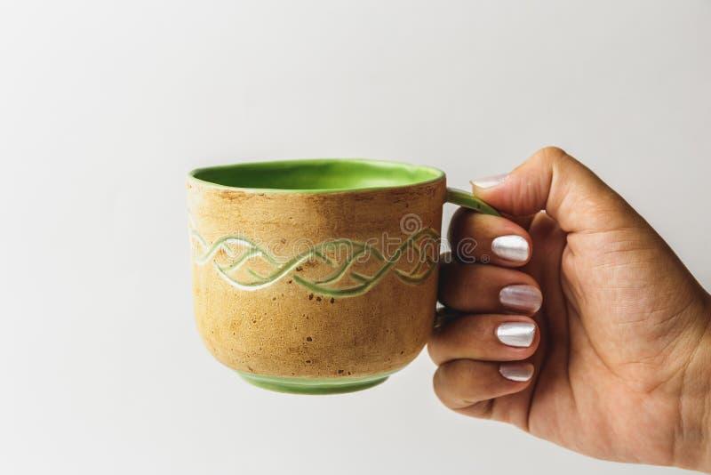 La main femelle étire une belle tasse faite main avec le thé ou le café photo libre de droits