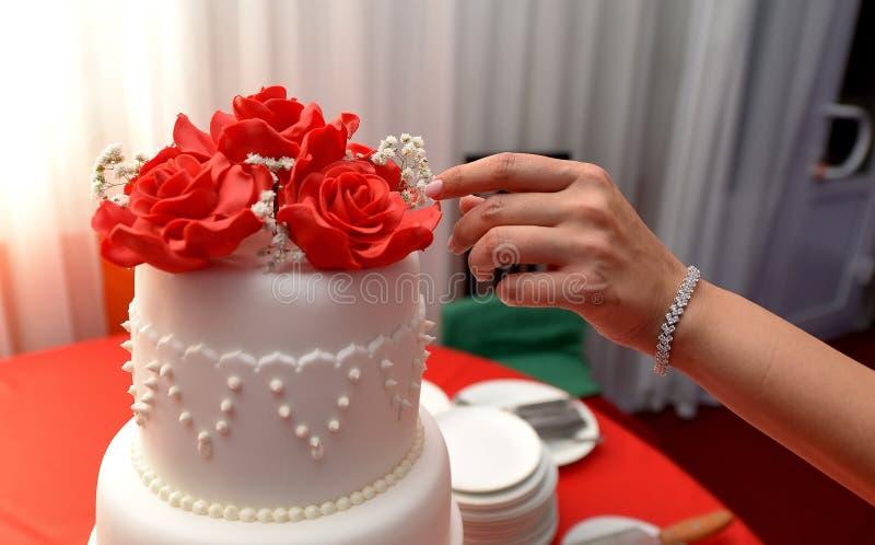 La main femelle ajuste des fleurs sur le gâteau de mariage photos libres de droits