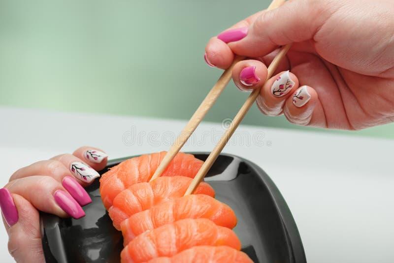 La main femelle avec la manucure magnifique prend des sushi avec un saumon lumière-salé d'un plat noir au moyen d'en bois images libres de droits