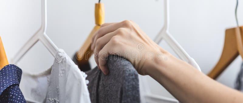 La main femelle choisit des vêtements sur un cintre photo libre de droits