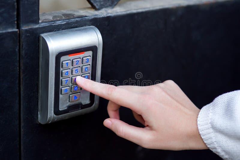 La main femelle compose le code d'accès sur la serrure électronique image libre de droits