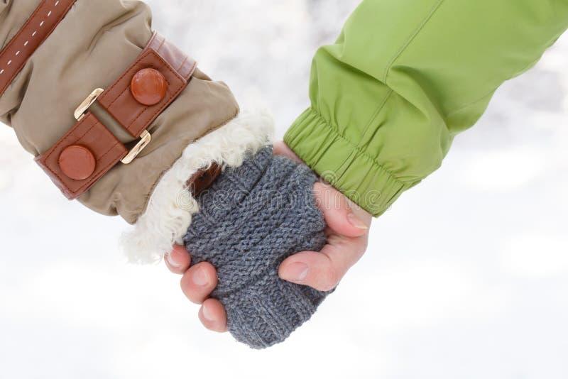 La main femelle dans le manteau d'hiver avec la fourrure blanche et le gris a tricoté le mitte photo libre de droits