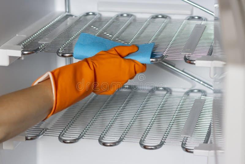 La main femelle dans les gants protecteurs essuient le réfrigérateur à l'intérieur photo stock