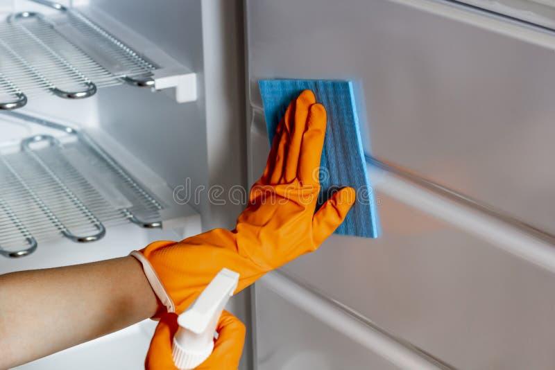 La main femelle dans les gants protecteurs essuient le réfrigérateur à l'intérieur image stock