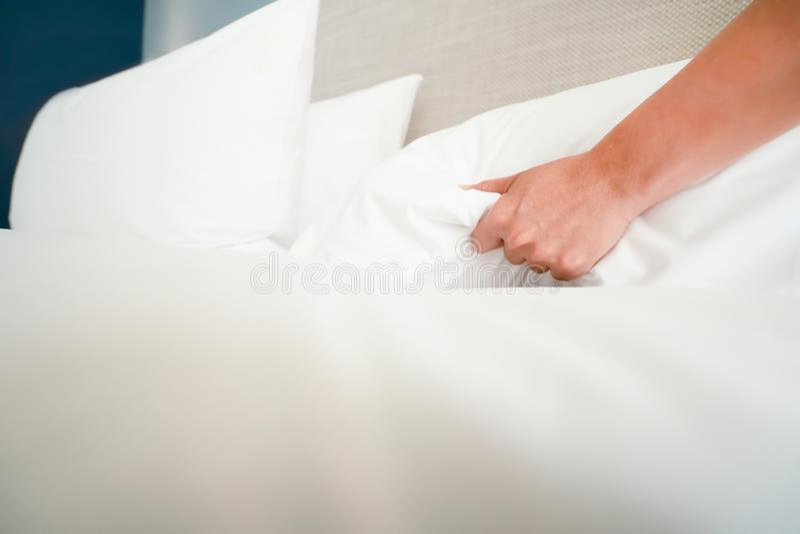 La main femelle a install? le drap blanc dans l'h?tel de la chambre photo stock
