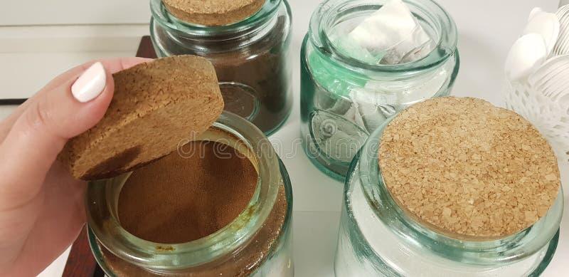 La main femelle ouvre la couverture de liège du pot en verre avec le café soluble image stock