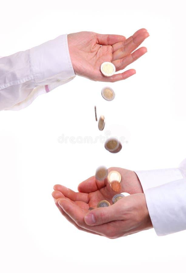 La main femelle pleuvoir à torrents en bas des pièces de monnaie dans les mains mâles images stock