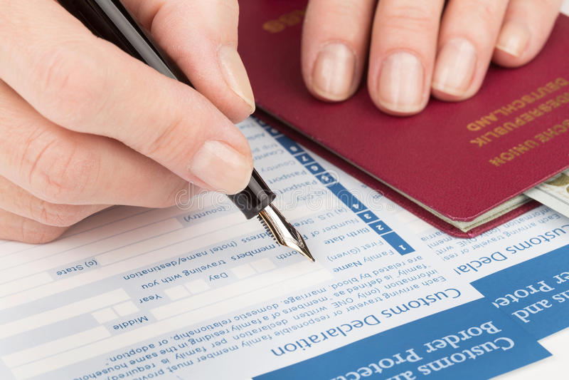 La main femelle remplit déclaration en douane photographie stock