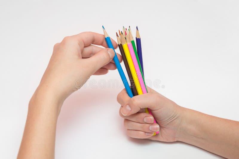 La main femelle tenant un poing autour de douzaine crayons, l'autre main sélectionne la couleur désirée image libre de droits