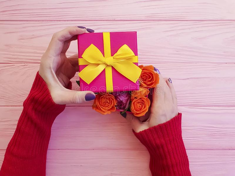 La main femelle tient l'arc romantique de célébration de salutation de surprise de boîte-cadeau, fleur rose sur le fond en bois r images libres de droits