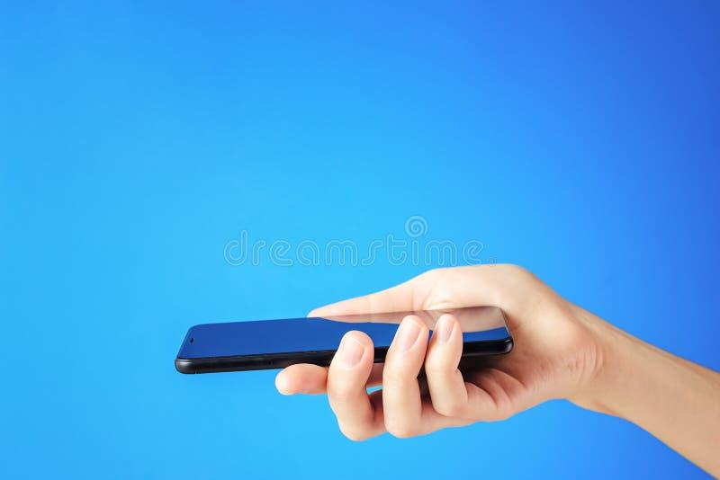La main femelle tient le smartphone noir sur le fond bleu images stock