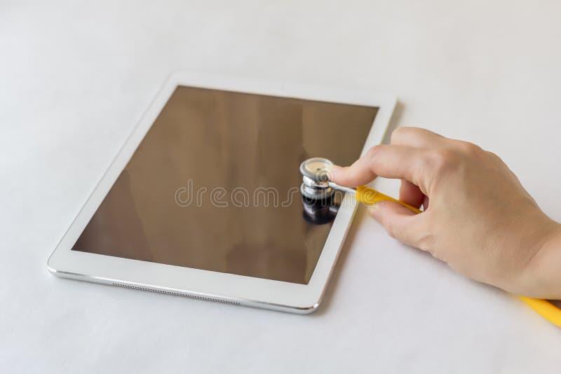 La main femelle tient un stéthoscope au-dessus de tablette photo stock