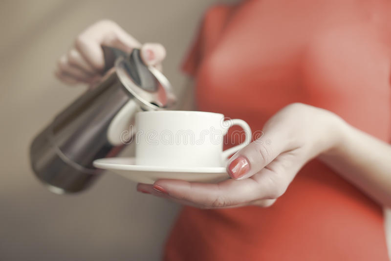 La main femelle verse une boisson dans la tasse du fabricant de café photo libre de droits