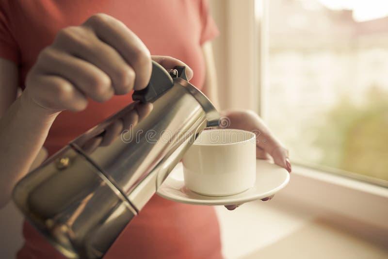 La main femelle verse une boisson dans la tasse du fabricant de café photos stock