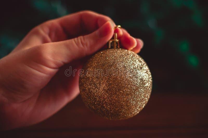 La main garde une boule d'or de Noël sur le fond vert et brun photos libres de droits