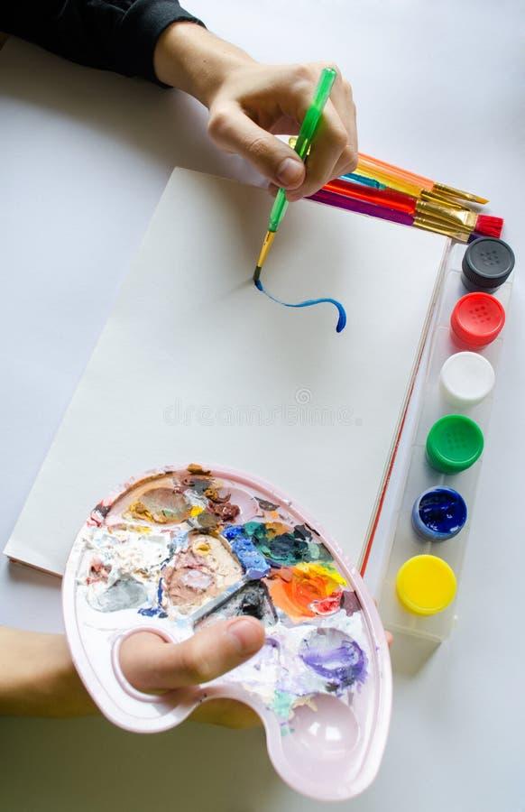 La main gauche dessine la brosse avec la peinture bleue sur le papier dans l'album avec le sev photographie stock libre de droits