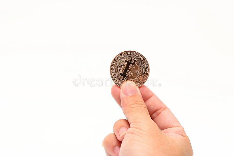 La main humaine du ` s tenant le bitcoin en bronze de cryptocurrency sur le blanc a isolé le fond avec l'espace de copie Concept  image stock