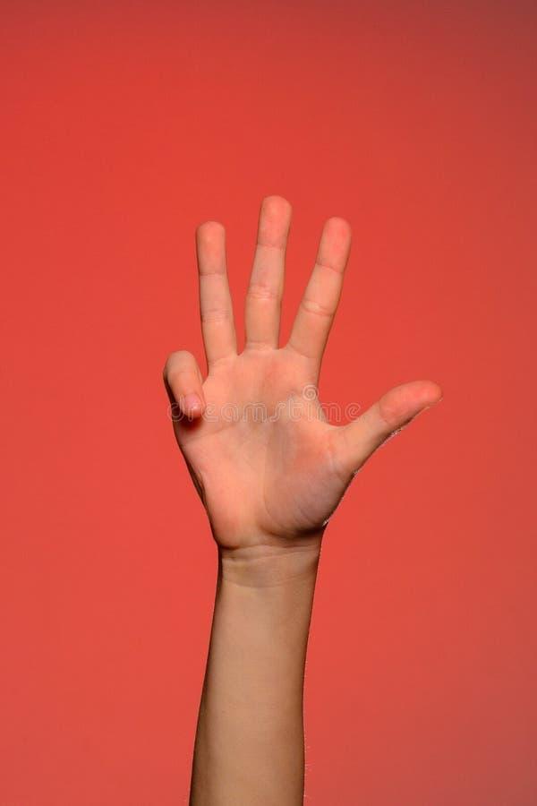 La main humaine montre quatre doigts d'isolement sur un fond rouge image libre de droits