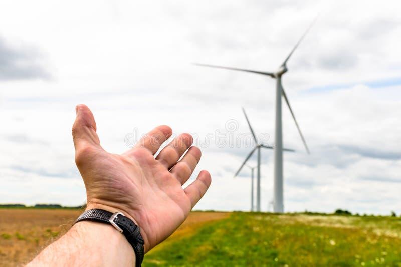La main humaine visant aux turbines d'énergie éolienne produisent de l'électricité image stock