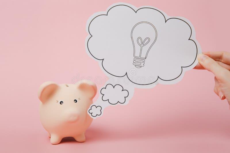 La main indiquent le nuage avec l'ampoule, idée près de la banque porcine d'argent d'isolement sur le fond rose en pastel de mur  image libre de droits