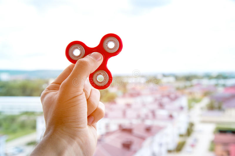 La main joue avec un fileur dans la perspective du paysage urbain dans le jouet remuant de main de ville images libres de droits