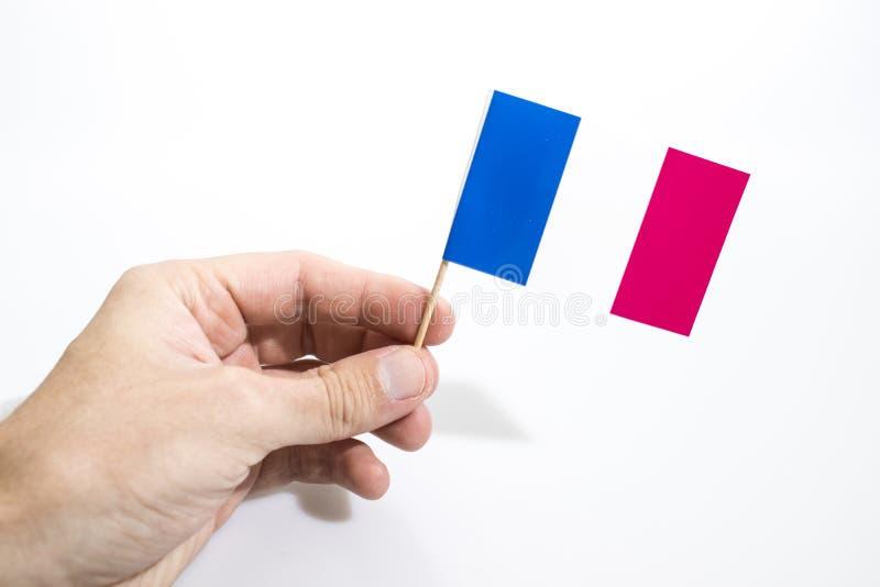 La main juge le drapeau français d'isolement à un arrière-plan blanc images stock