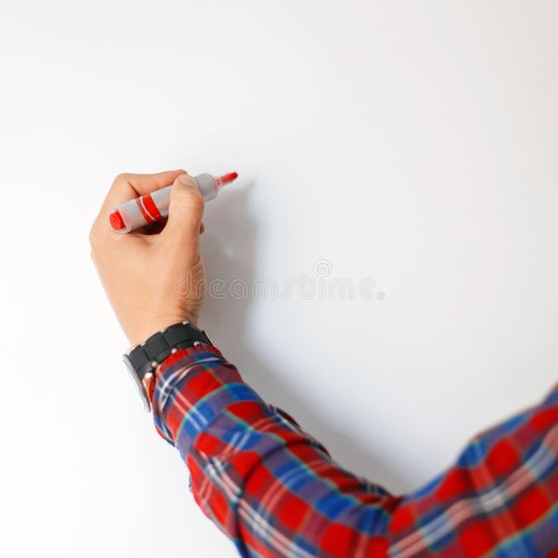 La main masculine avec un marqueur rouge dessine sur un conseil blanc images stock
