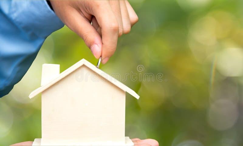 La main masculine tenant des pièces de monnaie et la banque porcine de maison épargnent l'argent, fond vert de nature Concept d'i photographie stock libre de droits