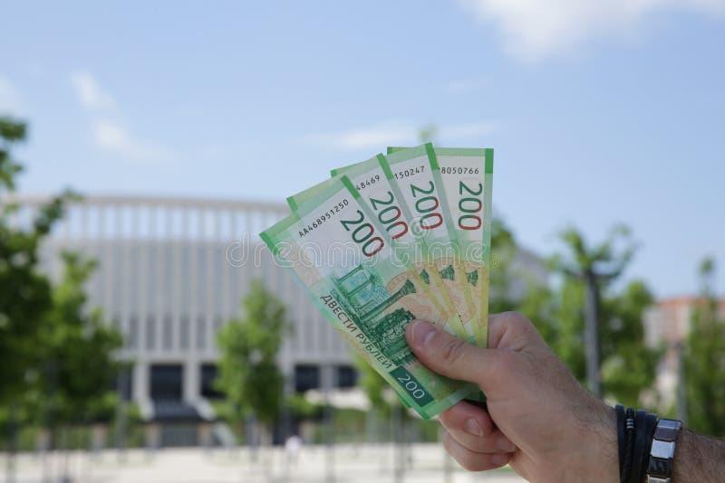 La main masculine tient un nouveau billet de banque russe deux cents roubles sur le fond d'un bâtiment et d'un ciel bleu Monnaie  image stock