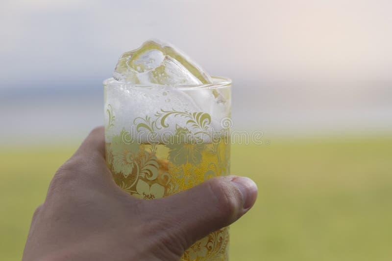 La main masculine tient un verre de bière avec de la glace et la nature de la montagne et du ciel égalisant photo libre de droits