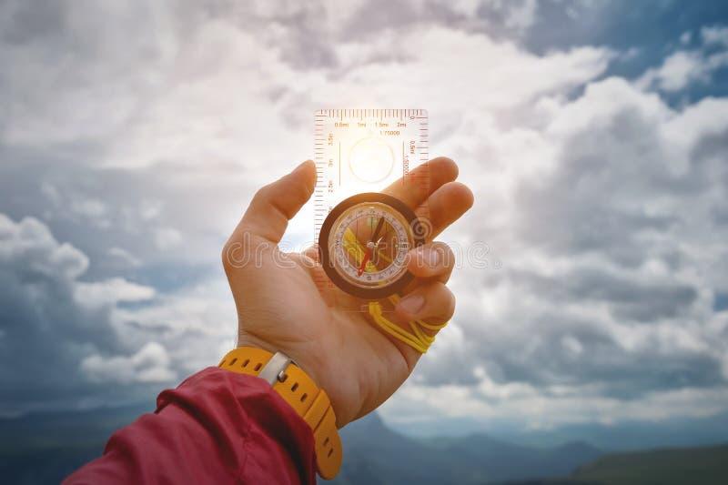 La main masculine tient une boussole magnétique sur le fond du ciel avec des nuages Le concept du déplacement et de la conclusion photos libres de droits