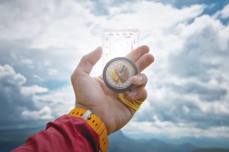La main masculine tient une boussole magnétique sur le fond du ciel avec des nuages Le concept du déplacement et de la conclusion image stock