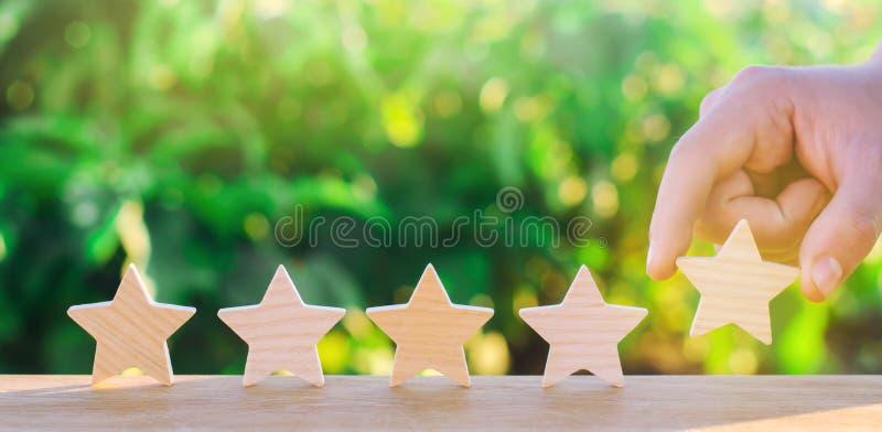 La main met la cinquième étoile en bois Obtenez la cinquième étoile Le concept de l'estimation des hôtels et des restaurants, l'é image stock