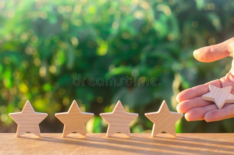 La main met/enlève la cinquième étoile en bois Obtenez la cinquième étoile Le concept de l'estimation des hôtels et des restauran photographie stock