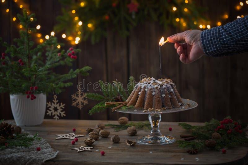 la main met le feu au cierge magique sur le gâteau de Noël images libres de droits