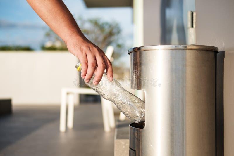 La main mettant les déchets en plastique de bouteille dans des déchets de déchets, la séparation de rebut et le plastique réutili images libres de droits